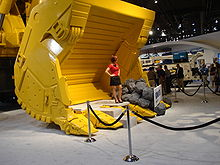 a female model, in a red top and black skirt, standing (with her hands on her hips) in a (bright yellow) bucket of an hydraulic shovel in the exhibit hall of MINExpo 2008. The model is standing behind a velvet rope discouraging trade show attendees from standing in the bucket. Another exhibit is visible in the background as is a group of approximately 12 attendees all but one of which appear to me men.
