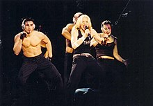 Madonna flanked by her bare-bodied dancers singing onstage.