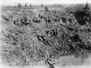 A black and white photograph of men in military uniform resting on the sloping sides of a large crater on a battlefield