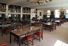 Uma sala cheia com muitas mesas e cadeiras e estantes que revestem as paredes.
