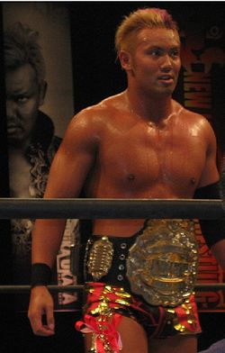 Kazuchika Okada with the IWGP Junior Heavyweight Championship belt in a wrestling ring