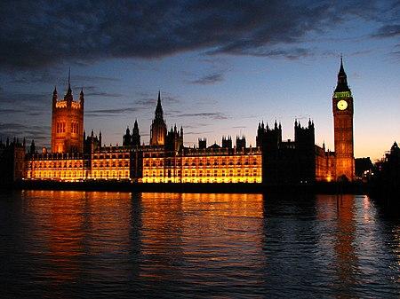 صورة لمبنى مستطيل الشكل منار بالضوء الغامر، معكوسة بالماء. لهذا المبنى عدّة أبراج يقع على كل طرف من أطرافها برج منها. يضم البرج الواقع على اليمين ساعة تضاء على مدار الساعة.