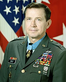 Portrait of a dark-haired white man wearing a military uniform with many ribbons, pins, and badges.