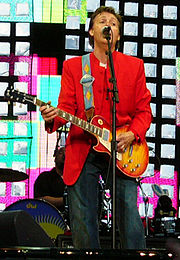 A colour photograph of McCartney, wearing a red coat and blue jeans playing an electric guitar and singing, while performing live on a stage.