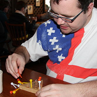 Peg solitaire - A man playing triangular peg solitaire at a Cracker Barrel restaurant.