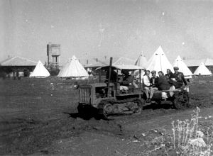 בשנים הראשונות של ההתישבות בדרום חברי הקיבוץ גרו בעיקר באוהלים, ולאט לאט החלו להיבנות הבתים. בתמונה טרקטור-זחל על רקע האוהלים