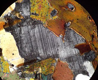 Plagioclase - A photomicrograph of a plagioclase crystal under cross polarized light. The plagioclase crystal shows a distinct banding effect called polysynthetic twinning.