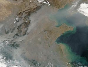 Global dimming - Dozens of fires burning on the surface (red dots) and a thick pall of smoke and haze (greyish pixels) filling the skies overhead in Eastern China. Smoke, pollution and other air particles are linked to global dimming. Photo taken by MODIS aboard NASA's Aqua satellite.