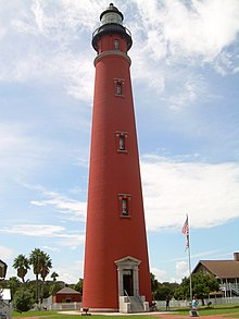 A tall red lighthouse, seen from the point of view of someone on the ground, is seen framed by a blue sky, with palm trees and a flagstaff in the background.