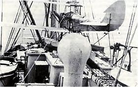 Rear view of biplane on floats aboard a ship