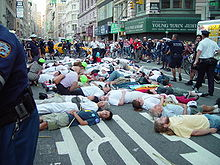 Street protest scene; people deliberately lying down on a busy city street, surrounded by onlookers and police