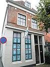 foto van Hoek Duinsteeg. Pand met gevelsteen, thans met rechte kroonlijst; pui gedicht en vensters op de verdieping XVIII. Voor- en zijgevel gepleisterd