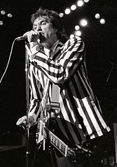 A man stands onstage with a guitar strapped across his chest. It hangs limp and unused, as he is focusing on singing into a microphone directly in front of him, which he grasps with his left hand, he wears a black-and-white, vertically striped suit.