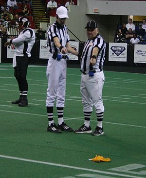Penalty flag - Officials point at a penalty flag lying on the field.
