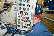 STS-128 Rick Sturckow adds his crew's patch to a wall of the Unity node
