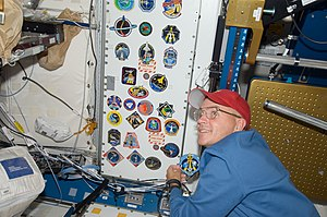 Frederick W. Sturckow - Sturckow adds the STS-128 mission patch to the wall of the Unity Node aboard the International Space Station.