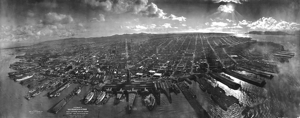 """San Francisco in ruins from Lawrence Captive Airship – 2000 feet [660 m] above San Francisco Bay – Overlooking waterfront. – Sunset over Golden Gate."" Market Street leads directly away from Ferry Building tower, center foreground."