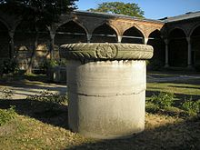 A stout cylindrical column in a courtyard in front of palatial arches of Islamic style