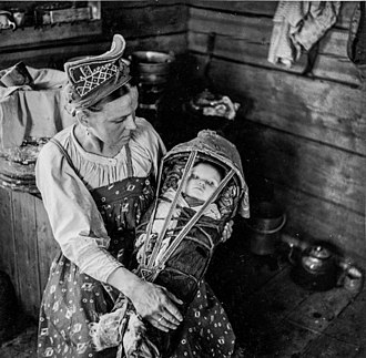 Cradleboard - A Skolt Sámi mother with her child in a ǩiõtkâm