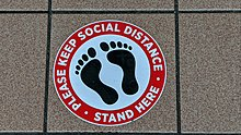 "Circular sign with a silhouette of bare feet, with text in a red border that says ""Please keep social distance • Stand here"""