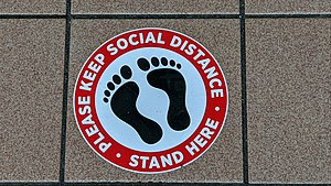 """Circular sign with a sillhouette of bare feet, with text in a red border that says """"Please keep social distance • Stand here"""""""