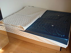 A bed with comforter pulled forward to show the water mattress