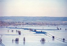 Photograph from elevation of flooded river flowing between snow covered fields. Hills in the distance.