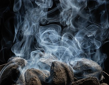 White smoke rising from charcoal briquettes as they start to catch fire and burn