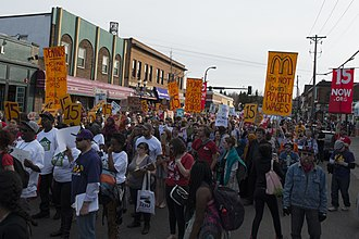 Minimum wage in the United States - Strike and protest march for a $15 minimum wage in Dinkytown, Minnesota part of the largest protests in 200 cities by 60,000 low-wage workers in US history on April 15, 2015.