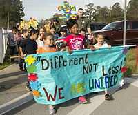 "A group of students and their family members carrying a sign saying ""Different Not Less: We Are United"" with different coloured puzzle pieces on the sign"
