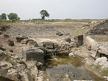 A shallow pool of water lies in front of stone blocks which were part of the port facilities of Sybaris.