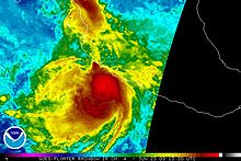 Colorized infrared satellite image of a tropical storm near the west coast of central Mexico. Intense convective activity, such as strong thunderstorms, are depicted by areas of bright red, concentrated around the center of the storm.