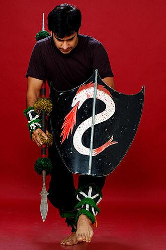Huyen langlon - Huyen langlon exponent holding spear and shield with serpent motif (pakhangba)
