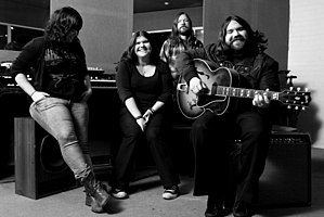 A black-and-white photo of The Magic Numbers leaning and sitting