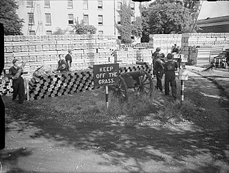Priddy's Hard - World War II: stacks of brass propellant cartridges along with tin boxes for bagged propellant charges are piled up on the front lawn of the Officers' Residence.