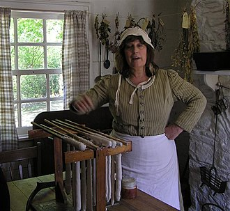 Ulster American Folk Park - The lady of the house, amongst other things she is demonstrating how wax candles are home-made