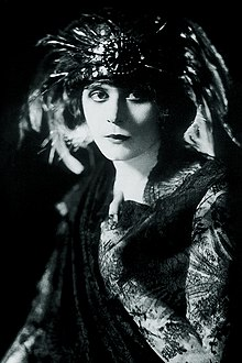 Black and white photo of a white woman wearing a feathered headdress and a dark gown with lace sleeves
