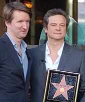 Two middle aged men stand side by side wearing suits and open-necked shirts. One is holding the plaue of a Hollywood star of fame