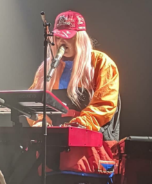 "Tones and I is standing behind a keyboard while also singing into a microphone. She wears red and white cap with the lettering ""The Kids Are Coming"". She also wears a multi-coloured jacket and is looking down at a sheet on a stand."