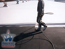 Top coating a commercial flat roof