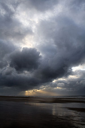 Dark and stormy clouds with sunlight breaking through in the background