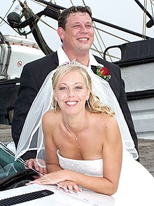 Colour photograph of a newly married couple.  A blond woman in a wedding dress posed in front of a man in a suit. The woman is leaning on a white car and looking directly at the camera; she has a white veil attached to a tiara and a white dress. The man is looking away from the camera with his collar open and a rose in his lapel. Both are smiling.