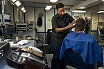 U.S. Navy Aviation Ordnanceman 3rd Class Shearra Miller cuts the hair of Airman Roan Collins April 24, 2013, while underway in the barbershop of the aircraft carrier USS Nimitz (CVN 68) 130424-N-KS651-098.jpg