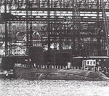 An incomplete submarine lays a rest; tall steel gantries and a dock dominate the background.