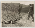 US Marines walk past a dead KPA soldier during the Korean War.png