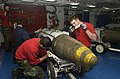 US Navy 030319-N-4142G-016 Aviation Ordinanceman 3rd Class Jovino Hernandez, and Aviation Ordinanceman Airman Matt Ethridge assemble Joint Direct Attack Munition (JDAM) bombs in the forward mess decks.jpg