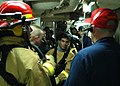 US Navy 030604-N-7902K-084 Damage Control Training Team Supervisor talk to the accessman (center), Seaman Rafael Rivera about the hose team procedures for accessing a fire filled space after a main space fire drill.jpg