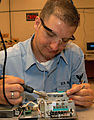 US Navy 031007-N-5134H-002 A Sailor solders a wire to a piece of electrical equipment.jpg