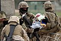 US Navy 050130-M-7981G-034 An Iraqi Security Force (ISF) soldier holds a baby while its mother goes to vote in the voting station.jpg