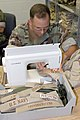 US Navy 050628-N-4034B-031 Storekeeper 3rd Class Patrick Faulkner sews nametags on Desert Utility Uniforms for Navy reservists recently mobilized.jpg